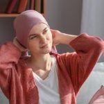 Cuidados de la piel durante la quimioterapia | Mujer con gorro alza la mirada.