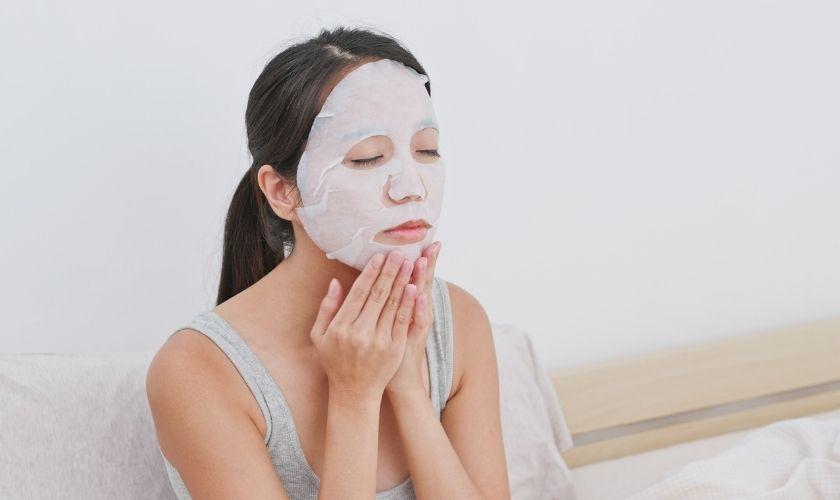 """Mujer japonesa aplicando máscara de tipo """"hoja impregnada""""."""