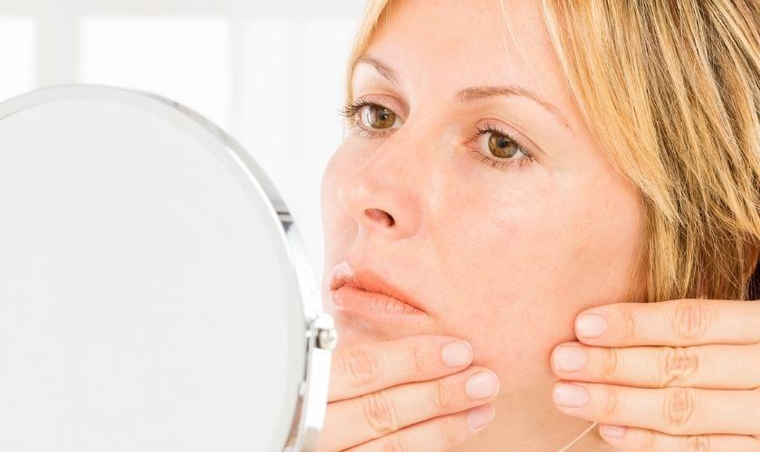 Cuidados diarios para el acné en adultos: mujer se revisa rostro frente a un espejo.