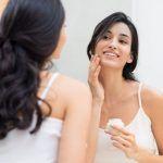 Mujer aplicándose crema hidratante en el rostro.