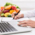 Estrategia nutricional en la psoriasis: Dra. escribiendo estrategia en ordenador portátil